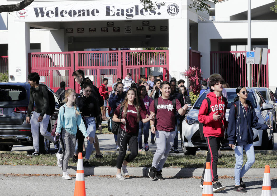 Students walk out of Marjory Stoneman Douglas High School, as part of a nationwide protest against gun violence, Wednesday, March 14, 2018, in Parkland, Fla. Organizers say nearly 3,000 walkouts a ...