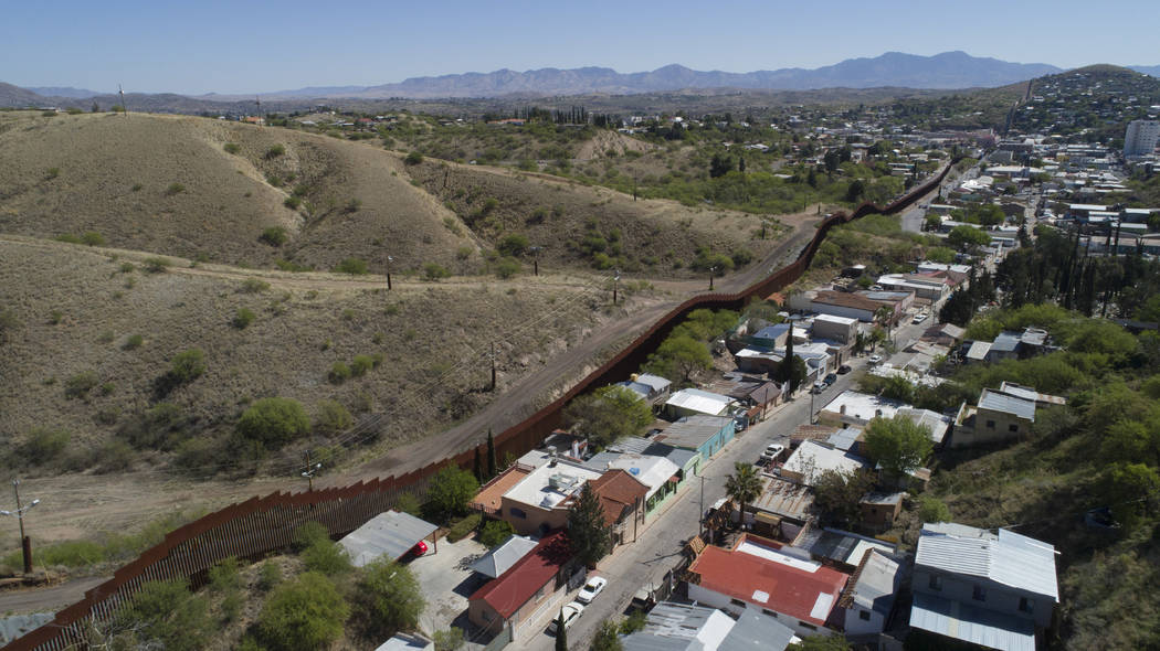 This April 2, 2017 file photo made with a drone, shows the U.S. Mexico border fence as it cuts through the two downtowns of Nogales, Ariz. A U.S. border patrol agent is going on trial for second-d ...