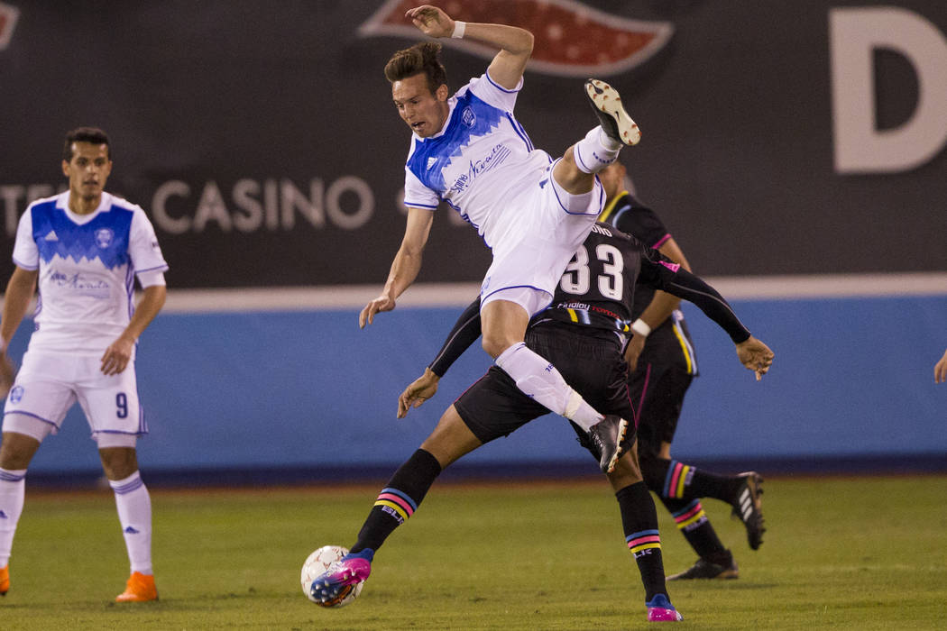 Reno 1868 FC's Danny Musovski (12) goes for the ball against Las Vegas Lights FC's  Miguel Angel Gardun~o (33) in the first half of the United Soccer League game at Cashman Field in  ...