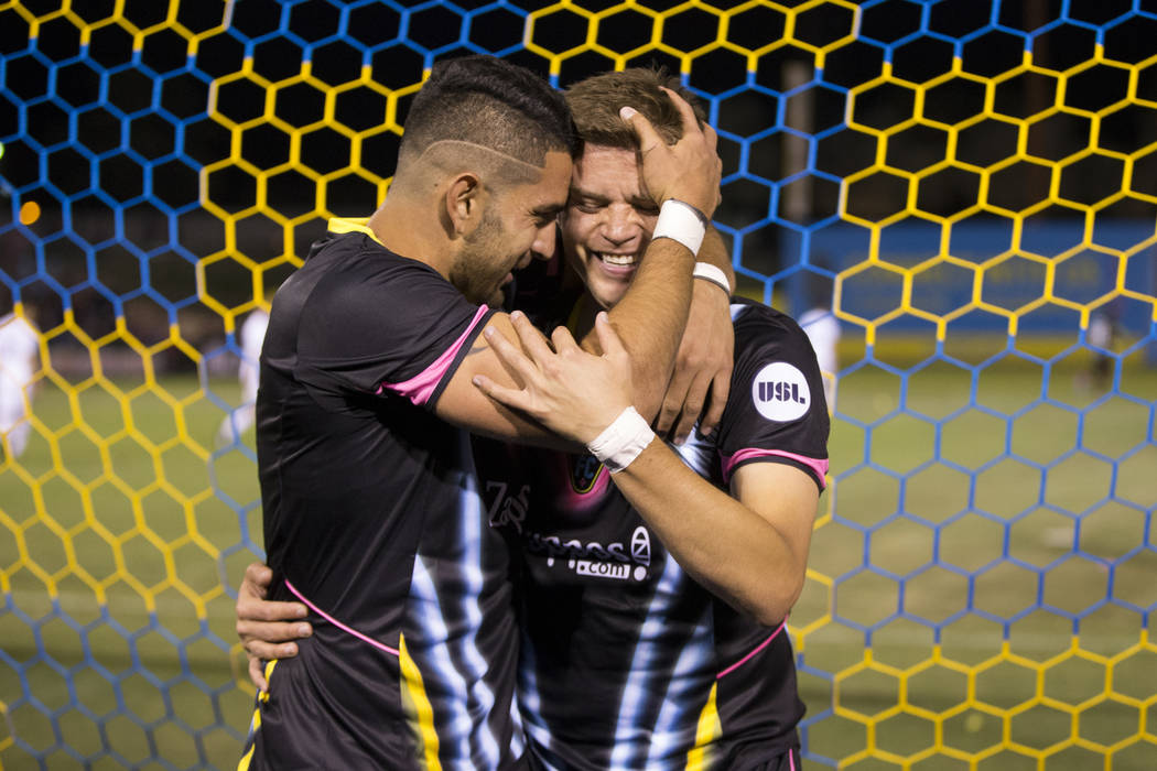Las Vegas Lights FC's Alex Mendoza (14), right, celebrates his goal with Marco Cesar Jaime Jr. (6) during the first half of the United Soccer League season home opener game against Reno 186 ...