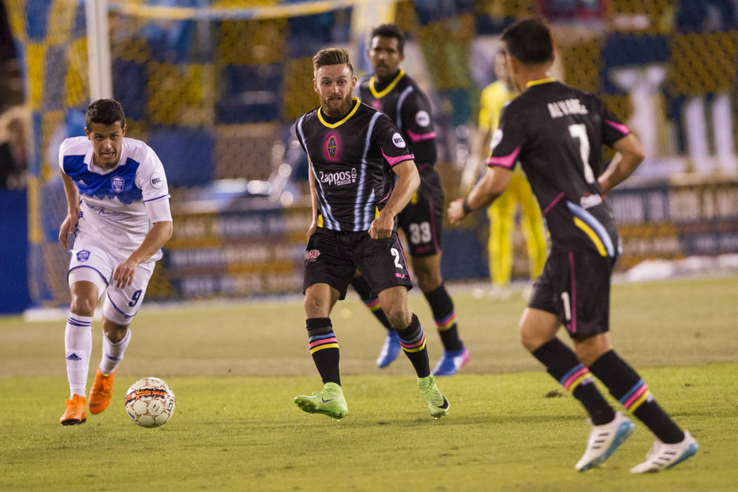 Las Vegas Lights FC's Zak Drake (2) makes a pass under pressure from Reno 1868 FC's Mark Gonzalez (9)  during the second half of the United Soccer League game at Cashman Field in Las ...