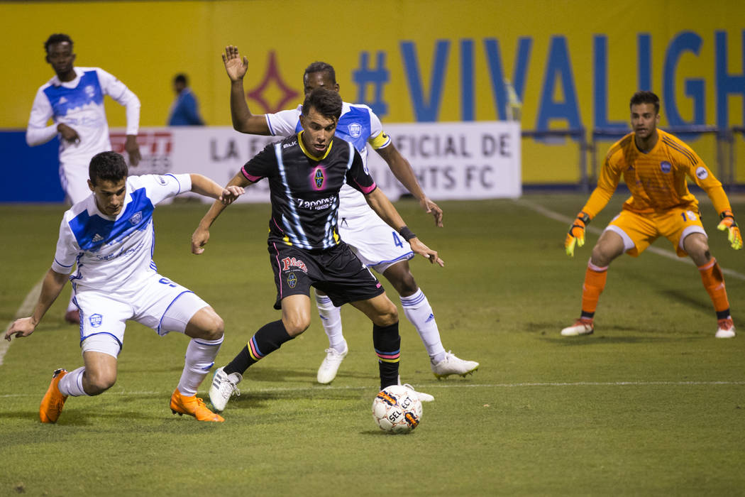 Las Vegas Lights FC's Carlos Alvarez (7) goes for the ball against Reno 1868 FC's Mark Gonzalez (9) during the second half of the United Soccer League game at Cashman Field in Las Ve ...