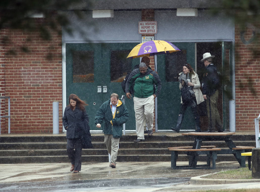 Teachers and school employees depart Great Mills High School, the scene of a shooting, Tuesday, March 20, 2018 in Great Mills, Md.  A teenager wounded a girl and a boy inside his Maryland high sch ...
