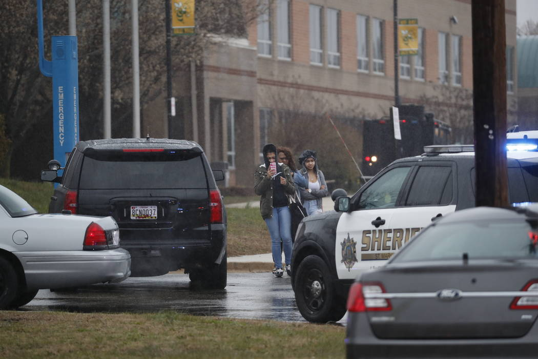 Two students and a mother leave Great Mills High School, the scene of a shooting, Tuesday morning, March 20, 2018 in Great Mills, Md. The shooting left at least three people injured including the  ...