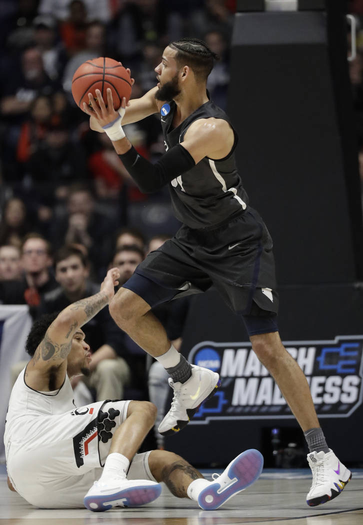 Nevada forward Cody Martin (11) looks to pass over Cincinnati guard Jarron Cumberland (34), during the first half of a second-round game in the NCAA college basketball tournament in Nashville, Ten ...