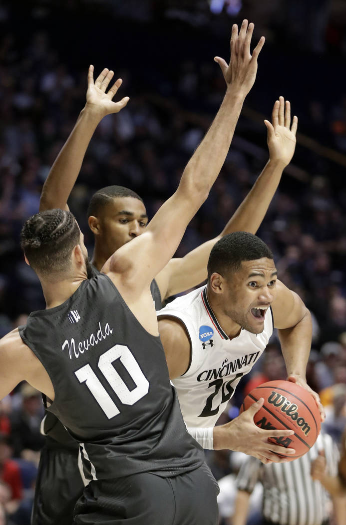 Cincinnati forward Kyle Washington (24) looks to pass under pressure from Nevada forward Caleb Martin (10), during the second half of a second-round game in the NCAA college basketball tournament  ...