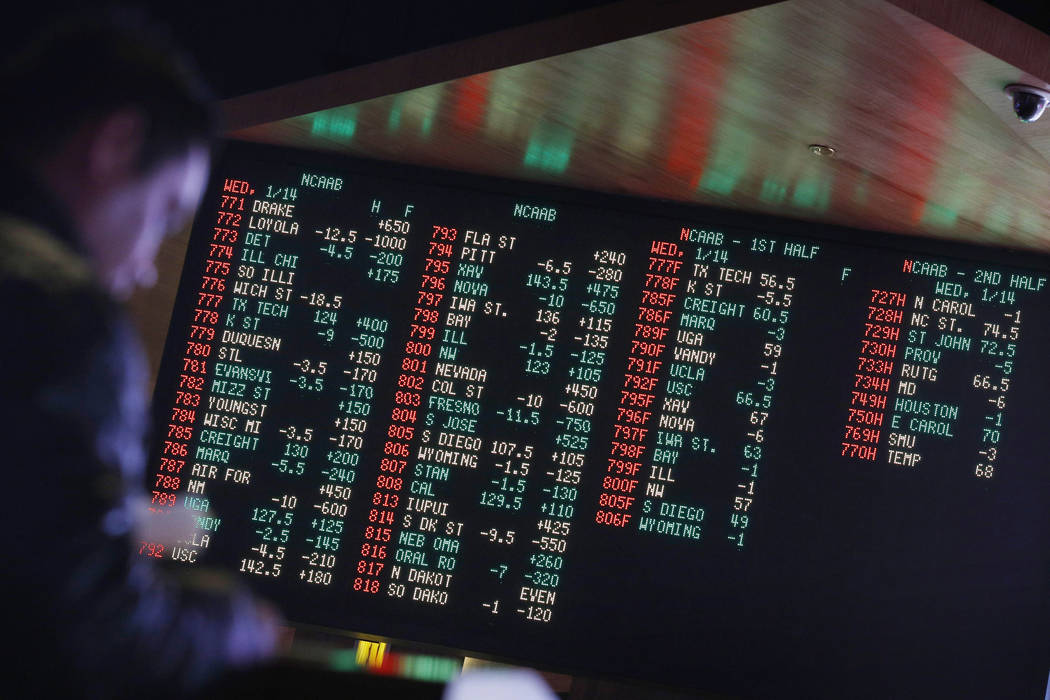 In this Jan. 14, 2015, file photo, odds are displayed on a screen at a sports book owned and operated by CG Technology in Las Vegas. (AP Photo/John Locher, File)
