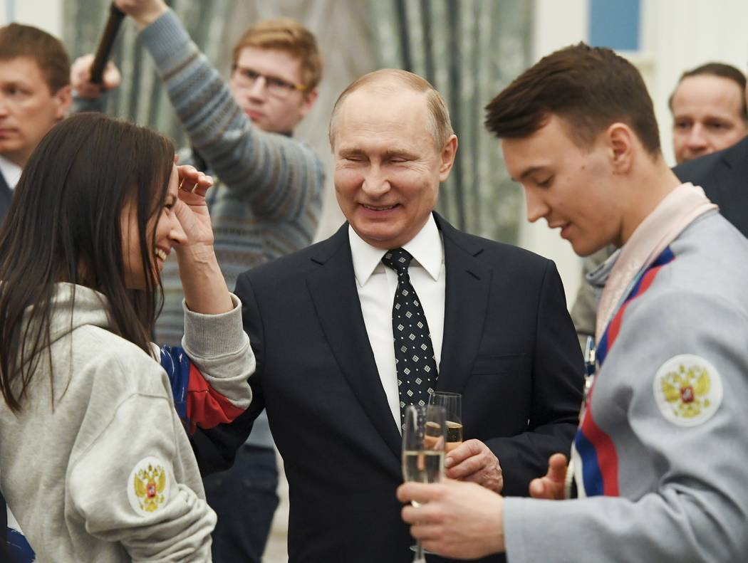 Russian President Vladimir Putin, center, toasts with Russian Paralympics Athletes who competed in the 2018 Pyeonchang Winter Paralympics, in the Kremlin in Moscow, Russia, Tuesday, March 20, 2018 ...