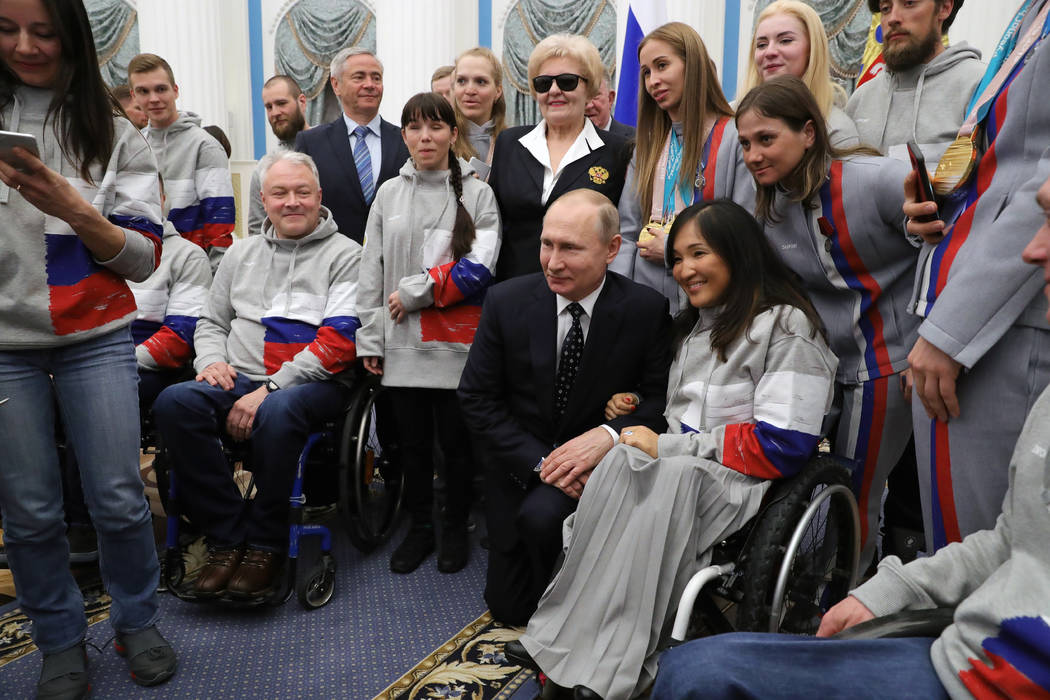 Russian President Vladimir Putin, center, poses for a photo with Russian Paralympics Athletes who competed in the 2018 Pyeonchang Winter Paralympics, in the Kremlin in Moscow, Russia, Tuesday, Mar ...