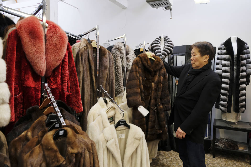 In this photo taken Friday, March 16, 2018, Benjamin Lin holds up a fur coat at the B.B. Hawk showroom in San Francisco. San Francisco could become the largest U.S. city to ban the sale of fur ite ...