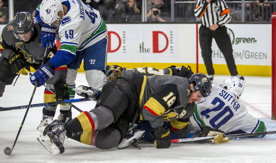 Vegas Golden Knights left wing James Neal (18) falls over Vancouver Canucks center Brandon Sutter (20) as he gets tangled up with goaltender Marc-Andre Fleury (29) after a shot attempt during the  ...
