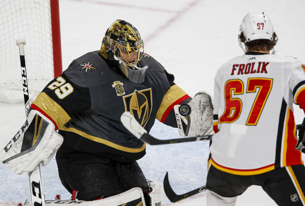 Vegas Golden Knights goaltender Marc-Andre Fleury (29) attempts to catch the puck as Calgary Flames right wing Michael Frolik (67) look for the rebound during the second period of an NHL hockey ga ...