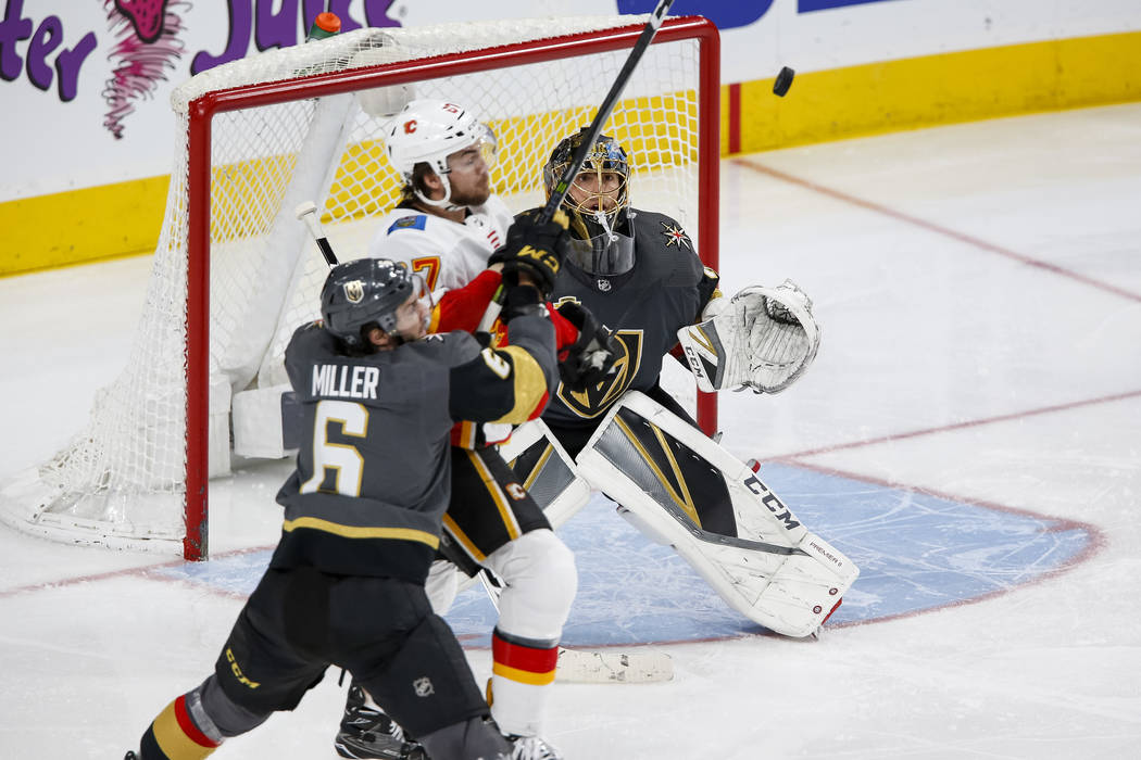 Vegas Golden Knights goaltender Marc-Andre Fleury, right, watches the puck as Knights defenseman Colin Miller (6) and Calgary Flames right wing Michael Frolik (67) battle for possession the second ...
