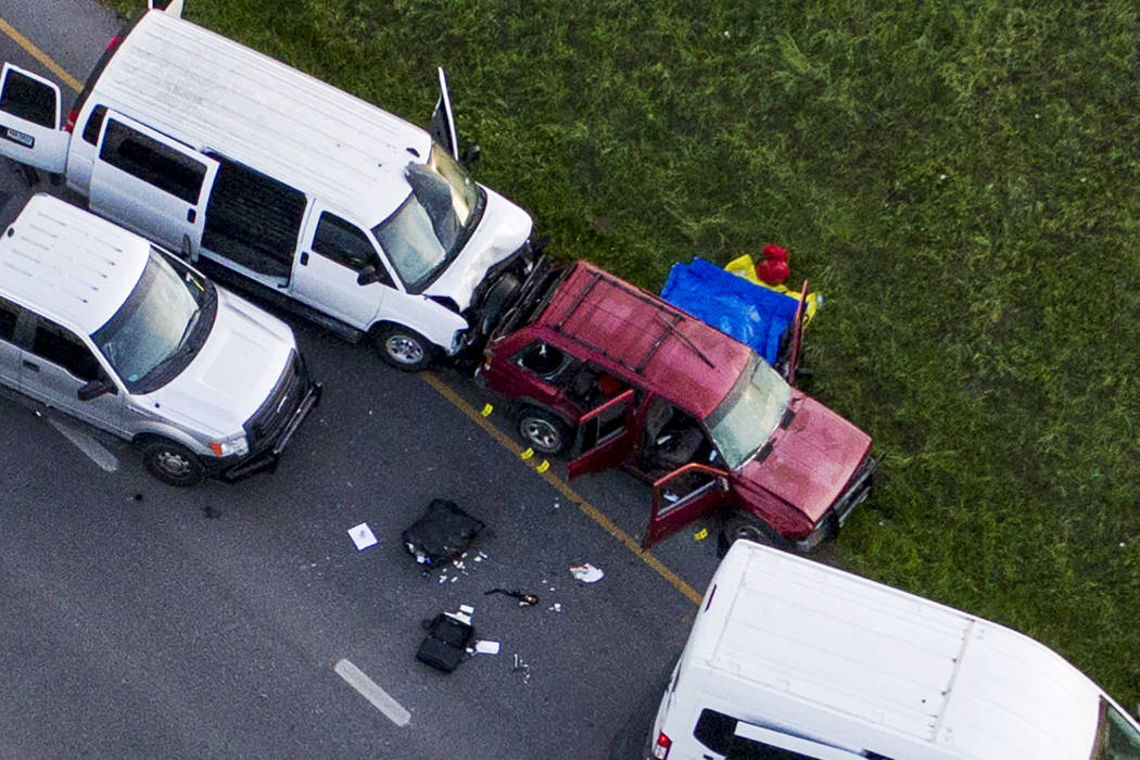 Officials investigate near a vehicle, center, where a suspect in the deadly bombings that terrorized Austin blew himself up as authorities closed in on him, in Round Rock, Texas, Wednesday, March  ...