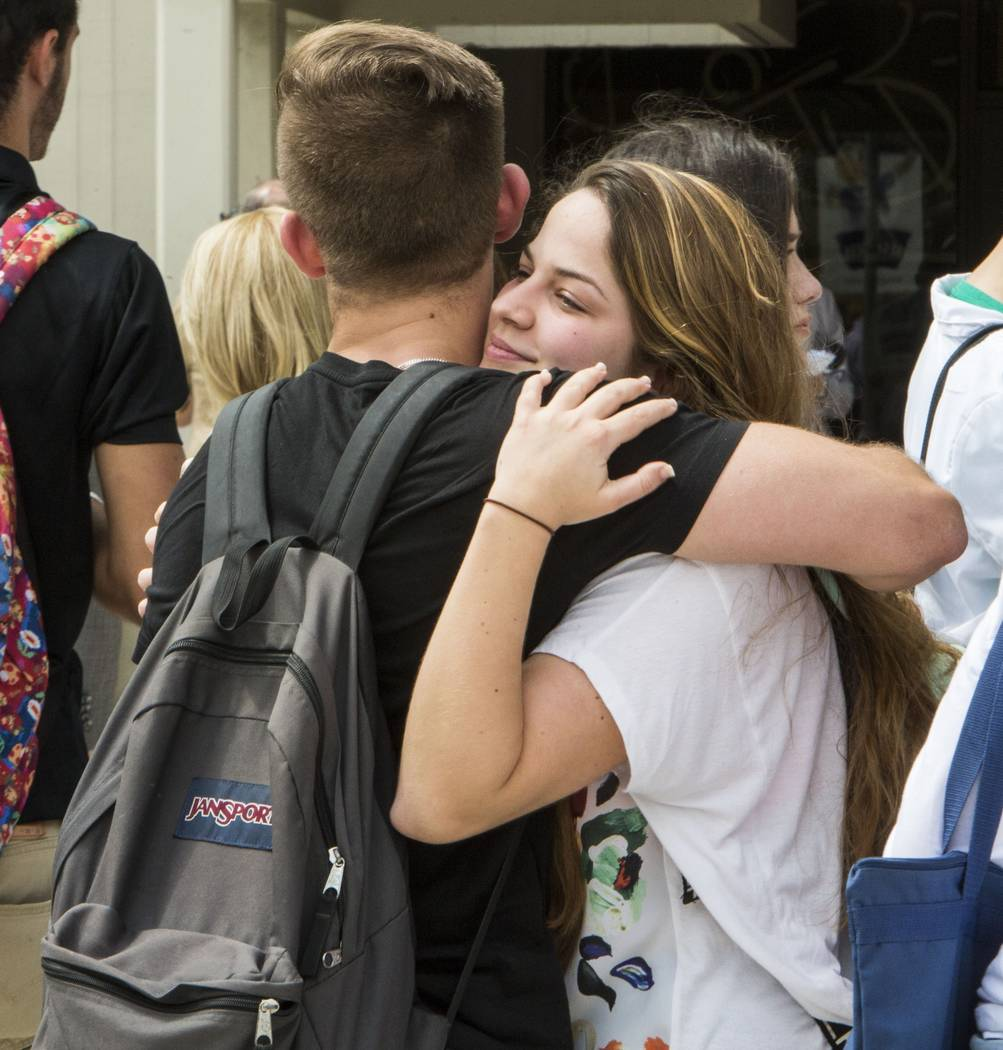 Florida International University sophomore Mariana Maciel embraces a friend after students, faculty and staff observed a moment of silence for the victims of the bridge collapse at the school four ...