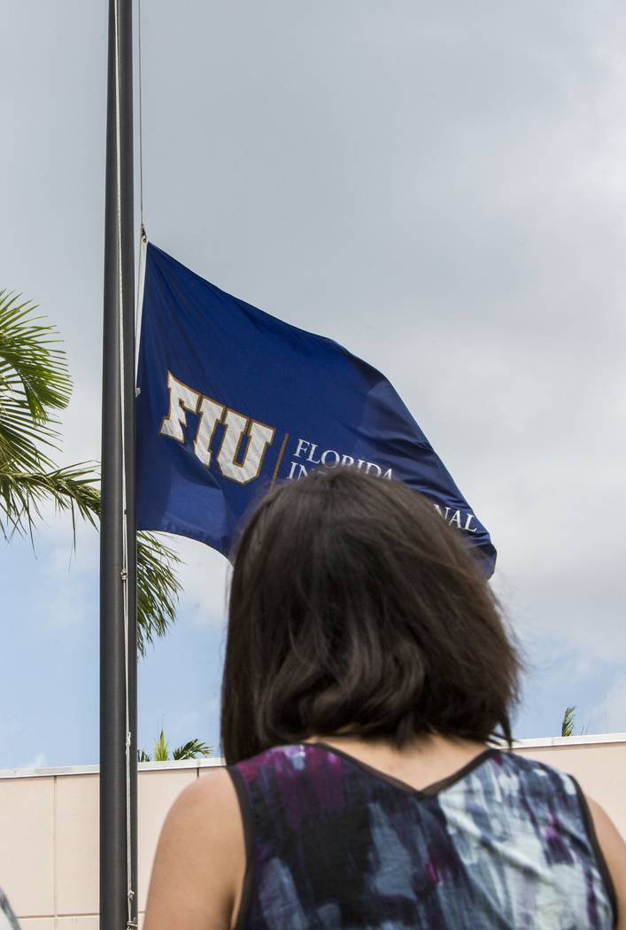 A Florida International University student observes a moment of silence for the victims of the bridge collapse at the school four days earlier, as the school flag flies at half-staff on the campus ...