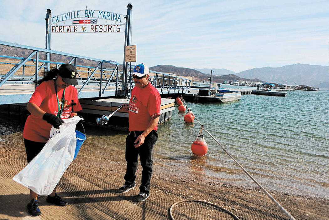 Alice Johnson, left, and Rick Potter pick up trash at Callville Bay Resort and Marina's launch ramp in Lake Mead National Recreation Area Saturday, Nov. 16, 2013. (Ronda Churchill/Las Vegas Revi ...
