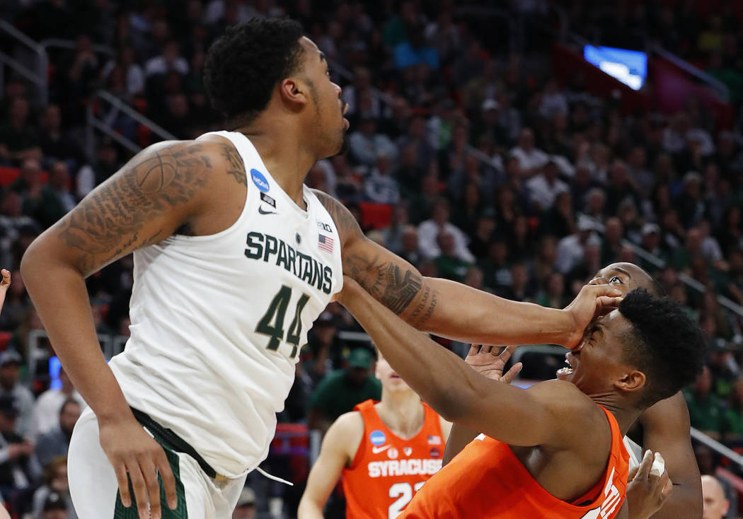Michigan State forward Nick Ward (44) puts a hand to the face of Syracuse guard Tyus Battle (25) during the second half of an NCAA men's college basketball tournament second-round game in Detroit, ...