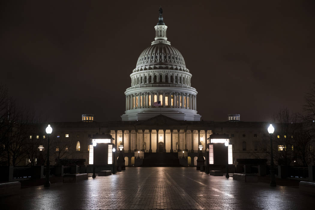 The Capitol is seen before dawn Wednesday after a night of negotiating on the government spending bill, in Washington, March 21, 2018. Talks over a $1.3 trillion omnibus bill are almost complete a ...