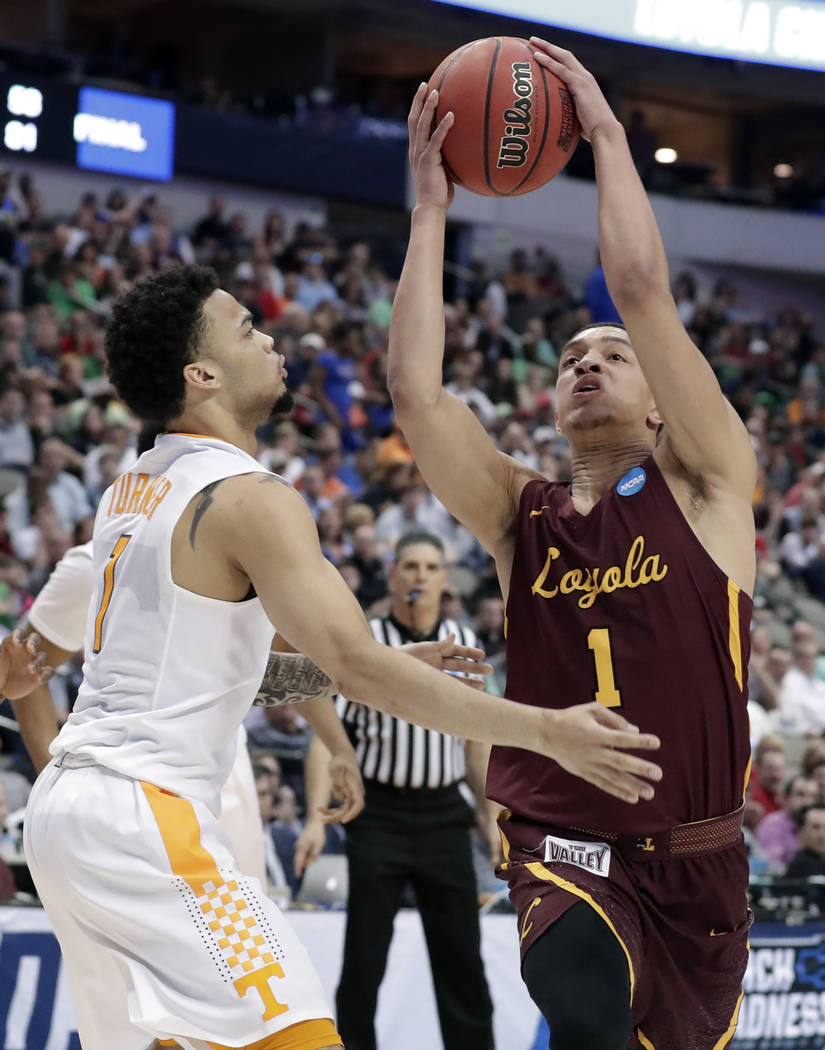 Tennessee guard Lamonte Turner, left, defends as Loyola-Chicago guard Lucas Williamson (1) drives to the basket during the second half of a second-round game at the NCAA men's college basketball t ...