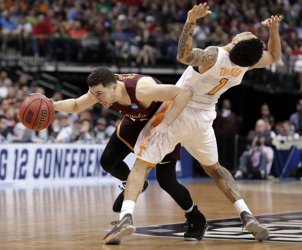 Loyola-Chicago guard Ben Richardson (14) is fouled by Tennessee guard Lamonte Turner during the second half of a second-round game at the NCAA men's college basketball tournament in Dallas, Saturd ...