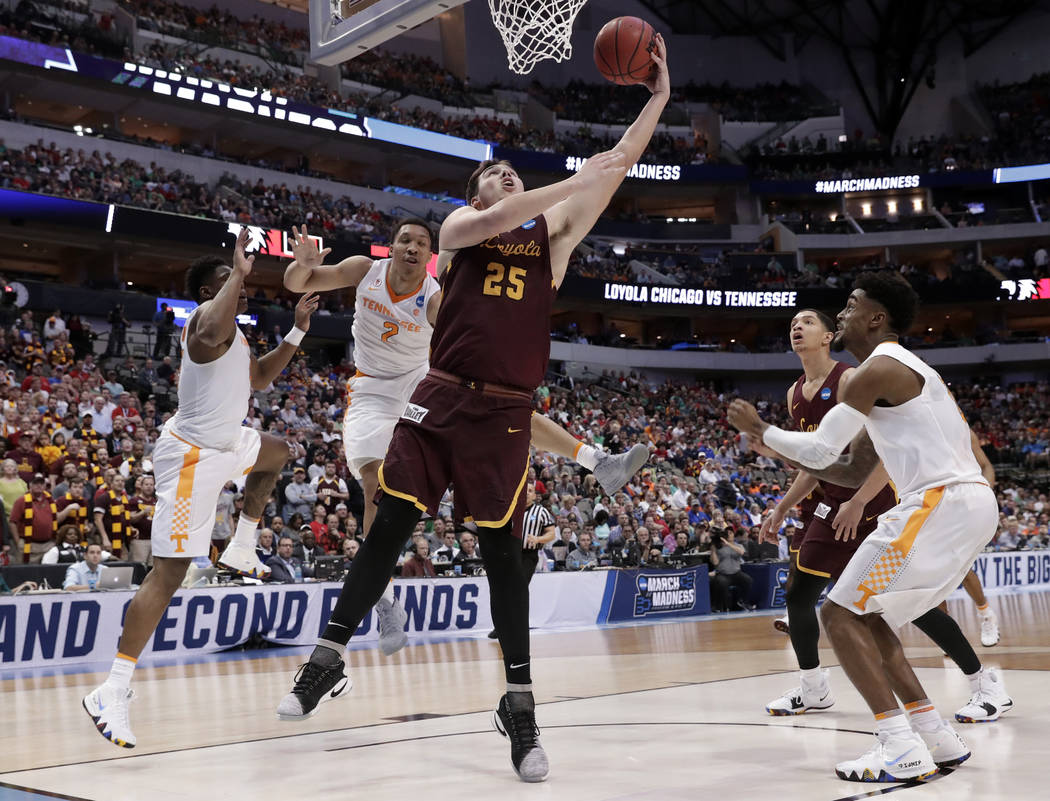 Loyola-Chicago center Cameron Krutwig (25) shoots after getting past Loyola-Chicago's Marques Townes, left, and Jake Baughman (2) during the second half of a second-round game at the NCAA men's co ...