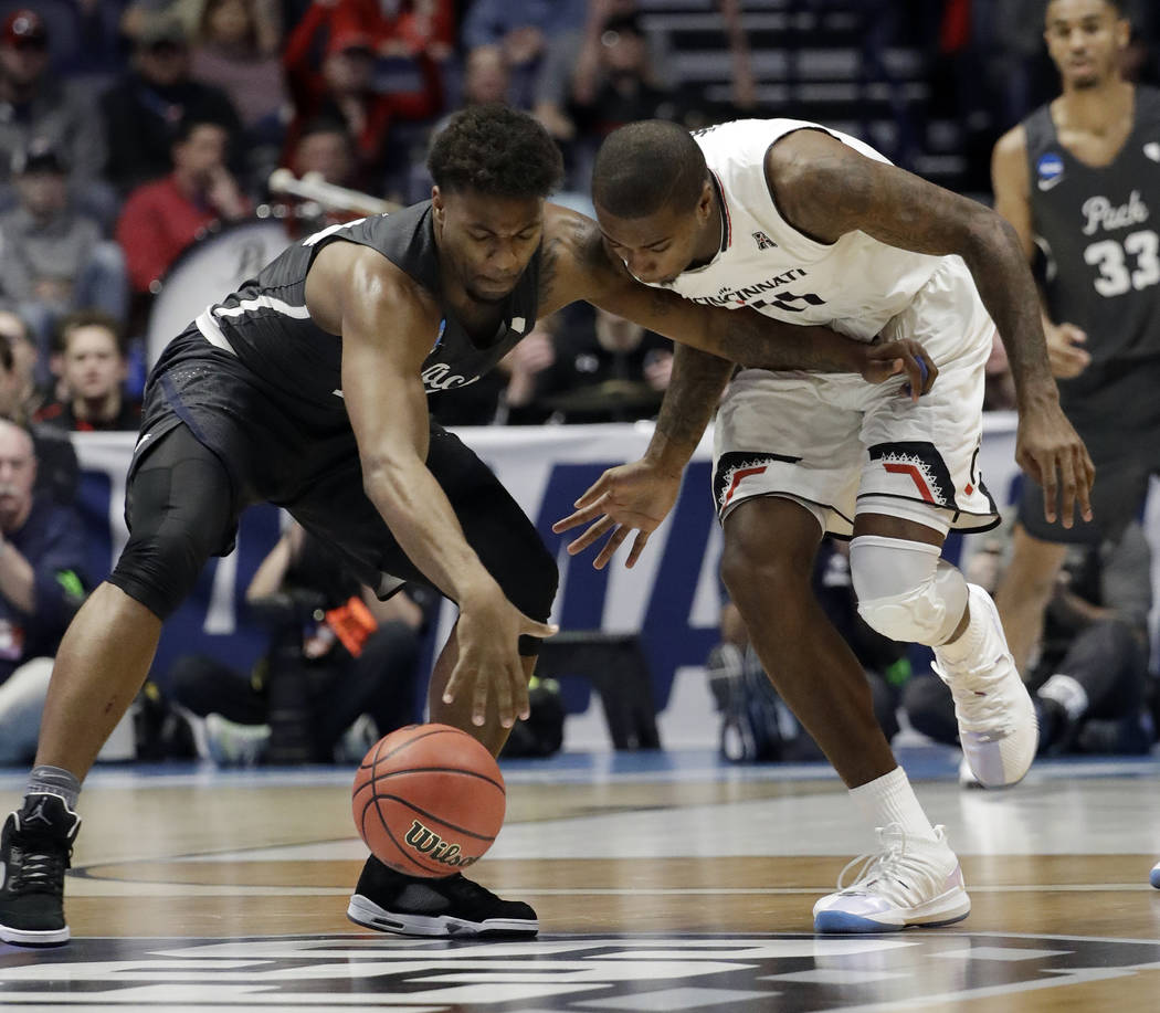 Nevada guard Jordan Caroline (24), left, and Cincinnati forward Gary Clark (11), go after a loose ball, during the first half of a second-round game in the NCAA college basketball tournament in Na ...