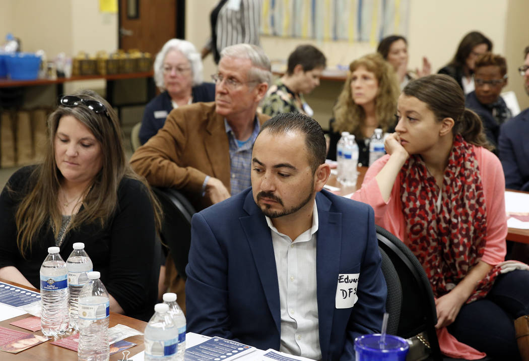 Tara Donohue, left, Edwardo Alvarez, center, and Juliana Whitney, right, attend an event to address permanent home needs for growing foster children population in Nevada on Friday, March 23, 2018, ...