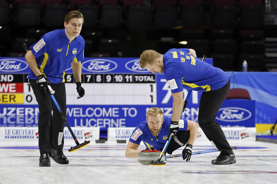 Team Sweden's Niklas Edin, center, delivers the rock to sweepers Oskar Eriksson, left, and Rasmus Wranaa during the round-robin games for the World Men's Curling Championship 2018ʡt the Orle ...