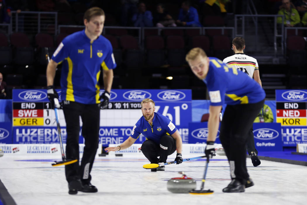 Team Sweden's Niklas Edin, center, delivers the rock to sweepers Oskar Eriksson, left, and Rasmus Wranaa during the  round-robin games for the World Men's Curling Championship 2018 at the Orleans  ...