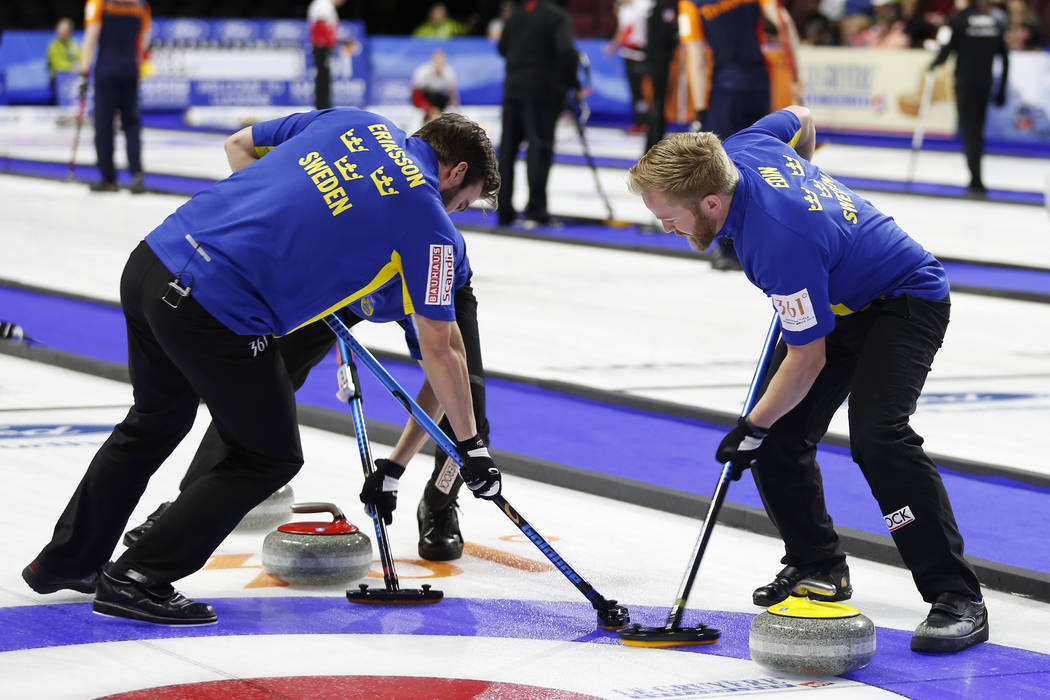 Team Sweden's Niklas Edin sweeps with Oskar Eriksson, left, during the round-robin games for the World Men's Curling Championship 2018 at the Orleans Arena in Las Vegas on Saturday, March 31, ...