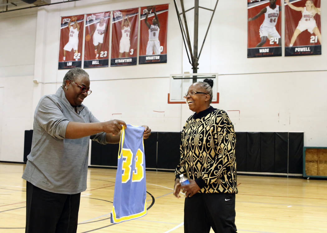 Women's basketball pioneer Cardte Hicks, left, displays Musiette McKinney's old jersey as they reunited after 30 years at UNLV's basketball practice court on Monday, March 26, 2018, in Las Vegas.  ...