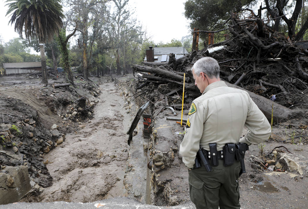 Santa Barbara County Sheriff Jeff Farmer checks the Montecito Creek to make sure it is flowing correctly Thursday March 22, 2018. A powerful storm spread more rain across California on Thursday, f ...