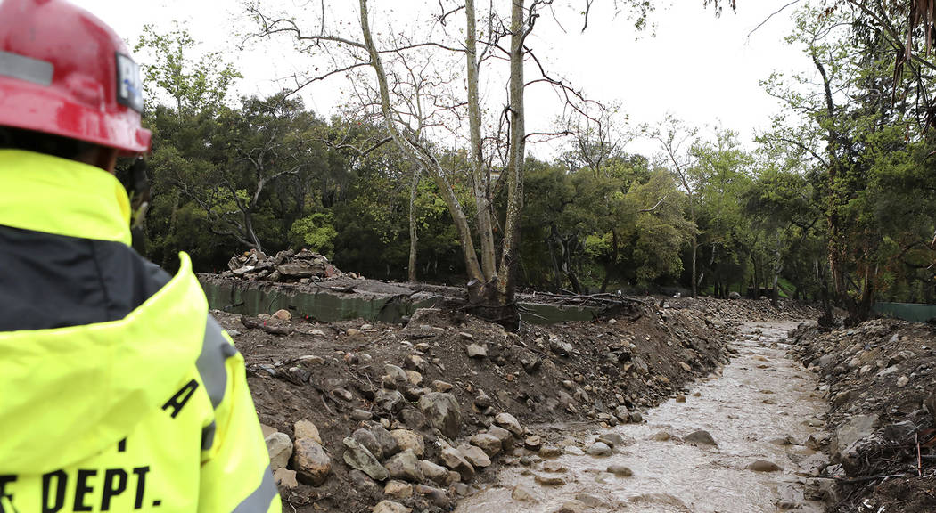 Santa Barbara County Fire Department Public Information Officer David Zaniboni looks at the water flowing down Montecito Creek next to a home that was destroyed in the Jan. 9 mudslide in Montecito ...