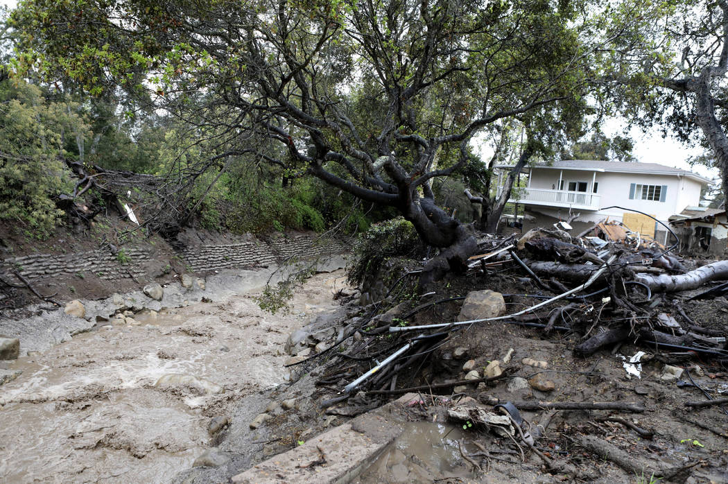 Water flows down Montecito Creek next a home that was destroyed in the Jan. 9 mudslide in Montecito, Calif., Thursday, March 22, 2018. A new round of heavy rain arrived Thursday, leaving authoriti ...