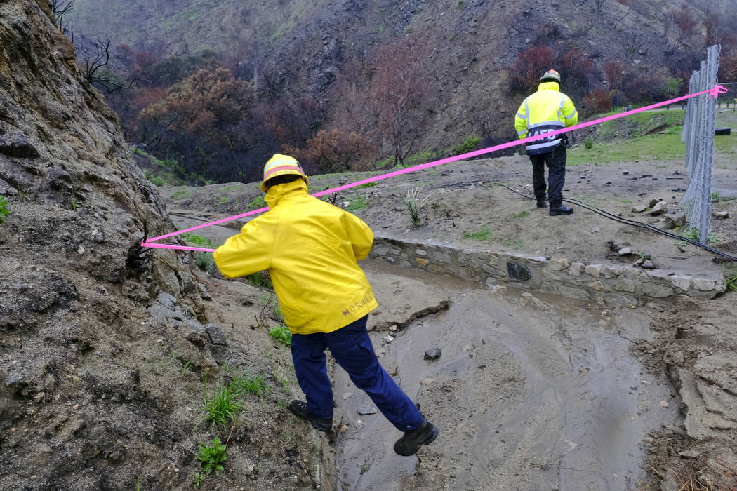 Firefighters close off an area of a mud slide caused by heavy rain along La Tuna Canyon Road in Los Angeles on Thursday, March 22, 2018, where mandatory evacuation orders had been in place amid mo ...