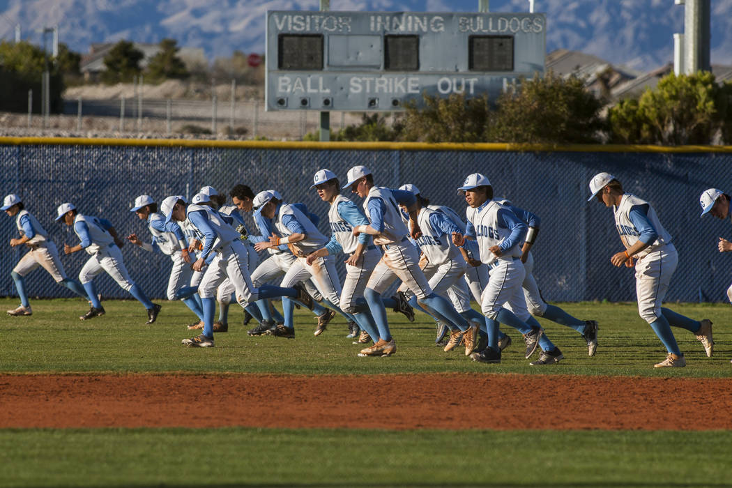 """Centennial players run across the outfield while """"Who Let the Dogs Out"""" plays over the loudspeakers after defeating Arbor View 11-2 at Centennial Hills High School in Las Vegas on Friday ..."""