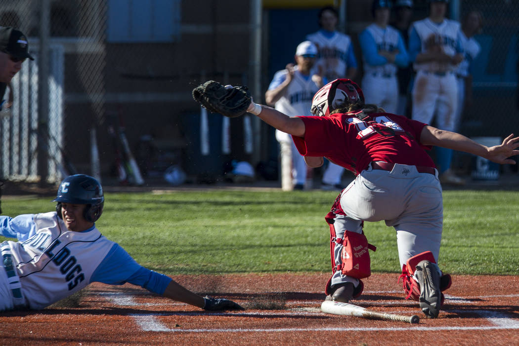 Centennial outfielder Trevor Wright slides in safe at home while Arbor View catcher Trey Urban disputes the call during the third inning at Centennial Hills High School in Las Vegas on Friday, Mar ...