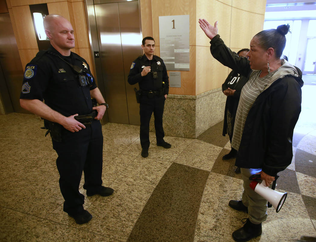 A pair of Sacramento Police Officers block access to the elevators of Sacramento City Hall to Allegra Taylor, right, and others during a demonstration, Thursday, March 22, 2018, in Sacramento, Cal ...