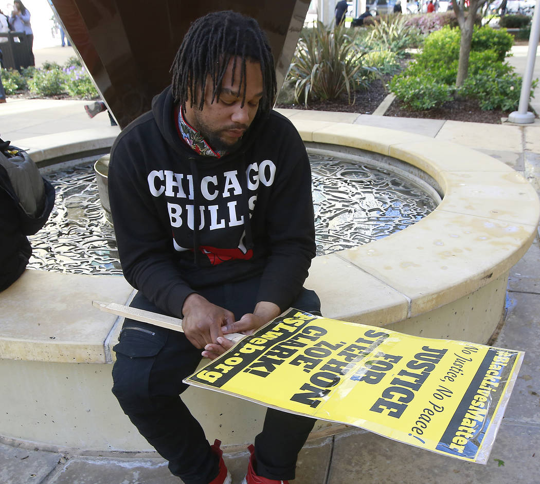 Andre Young, who says he is a cousin of shooting victim Stephon Alonzo Clark, stares at a protest sign during a demonstration, Thursday, March 22, 2018, over the shooting death of Clark by Sacrame ...