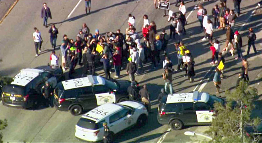 This photo from video provided by KCRA3 shows demonstrators protesting this week's fatal shooting of an unarmed black man and shutting down the Interstate 5 Freeway through downtown Sacramento, Ca ...