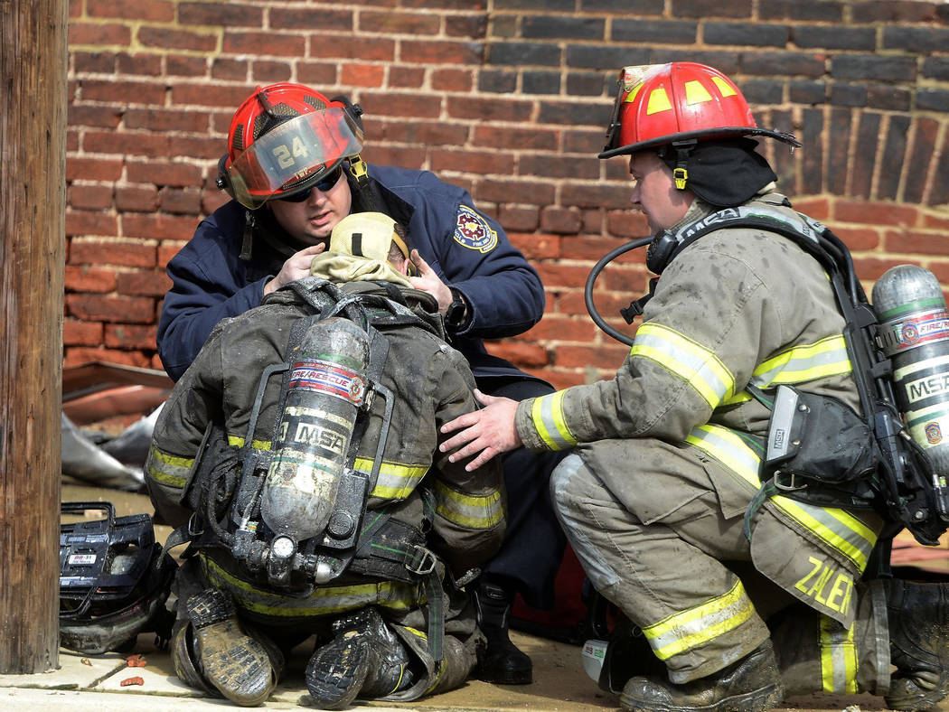 Rescue personnel tend to a fellow firefighter after a wall collapse at the scene of a fire in York, Pa., Thursday, March 22, 2018. York officials said part of the four-story building fell on firef ...