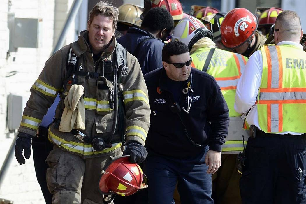 A firefighter walks away from where EMS work on a fellow responder who was injured when a wall collapsed at the scene of a fire in York, Pa., Thursday, March 22, 2018. York officials said part of  ...