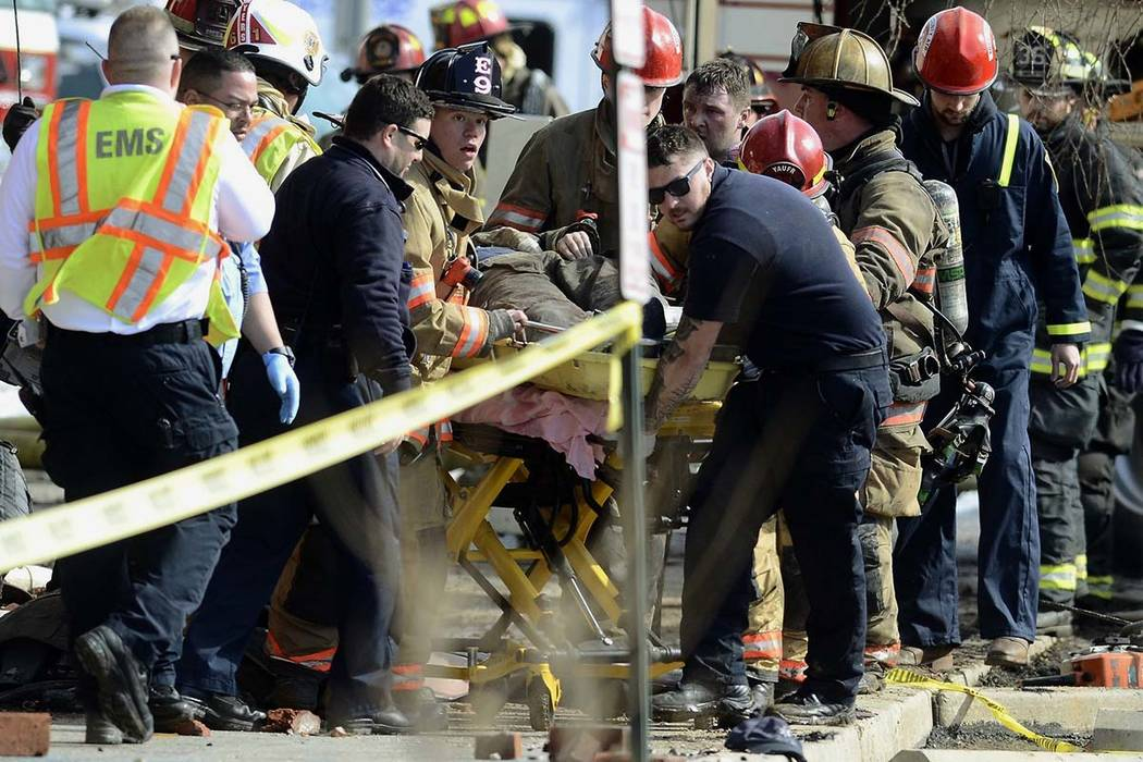 Emergency personnel move an injured firefighter to an ambulance after a wall collapse at the scene of a fire in York, Pa., Thursday, March 22, 2018. (John A. Pavoncello/York Dispatch via AP)