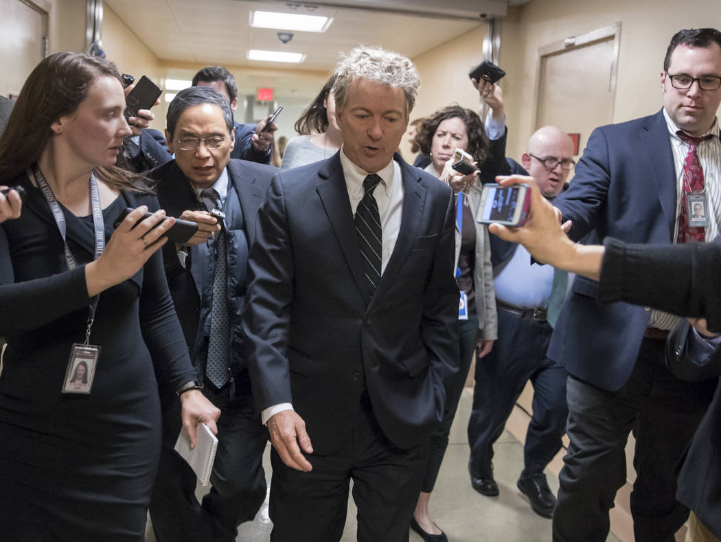 Sen. Rand Paul, R-Ky., walks to the Senate floor for a vote with accompanying reporters, on Capitol Hill in Washington, Wednesday, March 21, 2018. As the Senate gets closer to another government f ...