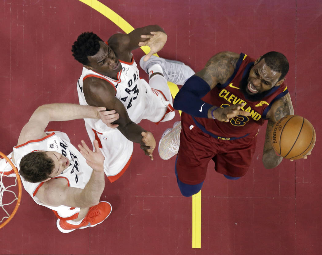 Toronto Raptors' Jakob Poeltl, left, and Pascal Siakam defend against Cleveland Cavaliers' LeBron James during the first half of an NBA basketball game Wednesday, March 21, 2018, in Cleveland. (AP ...