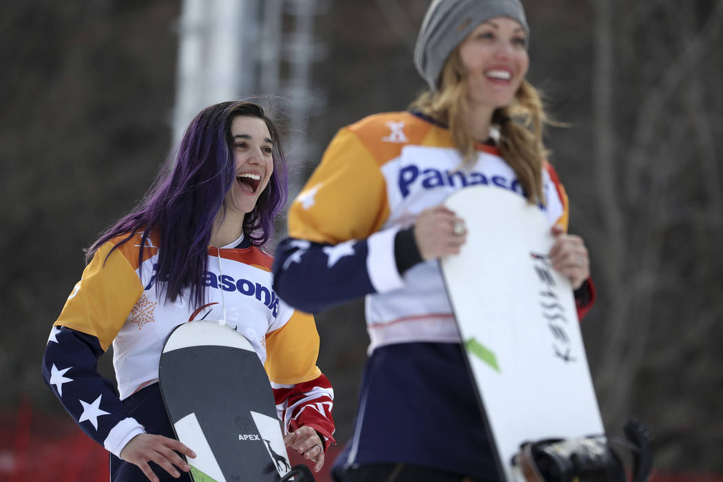 Winners of the Women's Snowboard Cross SB-LL1 event from left gold medalist Brenna Huckaby of United States and silver medalist Amy Purdy of United States react during a ceremony at the 2018 Winte ...