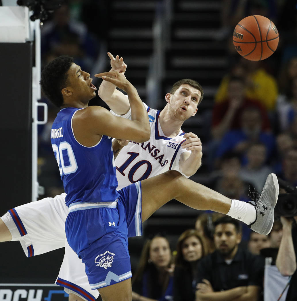 Kansas guard Sviatoslav Mykhailiuk (10) and Seton Hall forward Desi Rodriguez (20) chase a loose ball during the second half of an NCAA men's college basketball tournament second-round game Saturd ...