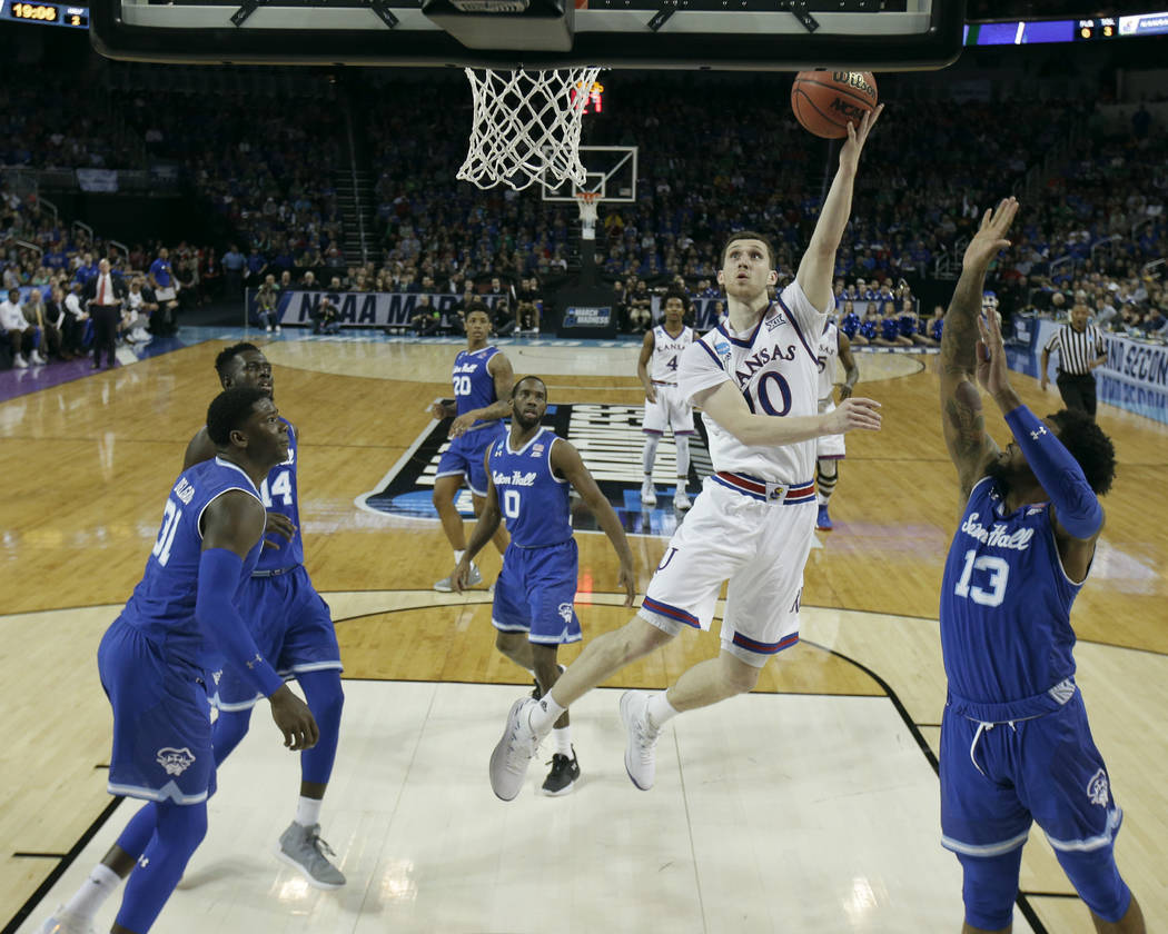 Kansas guard Sviatoslav Mykhailiuk (10) puts up a shot during the second half of an NCAA men's college basketball tournament second-round game against Seton Hall Saturday, March 17, 2018, in Wichi ...