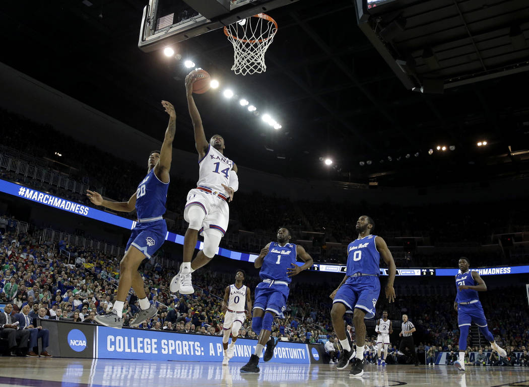 Kansas guard Malik Newman (14) gets pst Seton Hall forward Desi Rodriguez (20) to put up a shot during the second half of an NCAA men's college basketball tournament second-round game Saturday, Ma ...